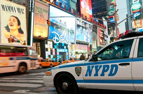 Street scene from Broadway at Times Square at twilight - NY Police Department car on duty in the foreground with traffic and numerous illuminated billboards in the background.
