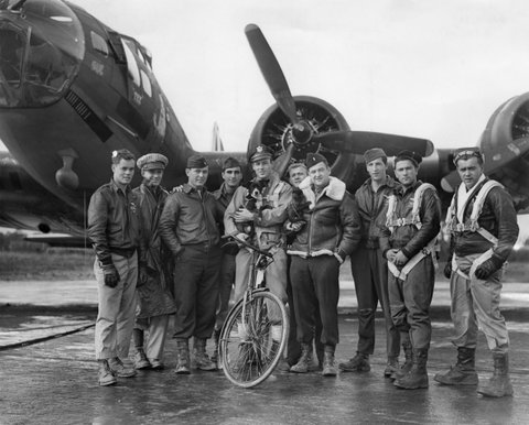 American pilot Robert W Biesecker and his crew standing by their B-17 Flying Fortress bomber 'Honey Chile' at a US Eighth Air Force station in England, 18th October 1943. With them are their two mascots, a dog named Scrappy and a monkey named Joe. (Photo by M. McNeill/Fox Photos/Hulton Archive/Getty Images)