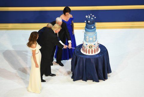 US President Donald Trump, the first lady Melania Trump, US Vice President Mike Pence, and his wife Karen cut a cake after dancing at the Armed Services ball at the National Building museum following Donald Trump's inauguration as the 45th President of the United States, in Washington, DC, on January 20, 2017.  / AFP / JIM WATSON        (Photo credit should read JIM WATSON/AFP/Getty Images)