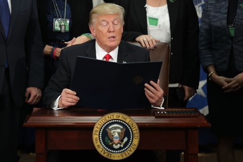 WASHINGTON, DC - JANUARY 25:  (AFP OUT) U.S. President Donald Trump (C) reads from one of the two executive orders he signed during a visit to the Department of Homeland Security January 25, 2017 in Washington, DC. Trump signed two executive orders related to domestic security and to begin the process of building a wall along the U.S.-Mexico border.  (Photo by Chip Somodevilla/Getty Images)