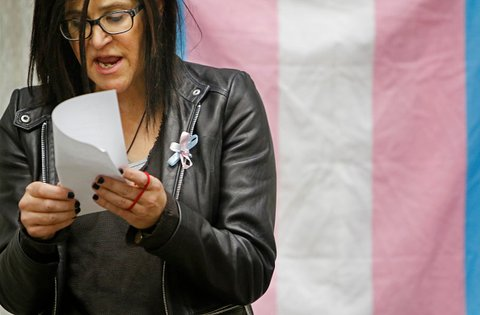 PORTLAND, ME - NOVEMBER 20: While standing in front of the Transgender Pride flag, Gia Drew, president of Maine TransNet, reads a portion of over 200 names of transgender people who were murderered globally in the last year during a Transgender Day of Remembrance.  (Photo by Jill Brady/Portland Press Herald via Getty Images)