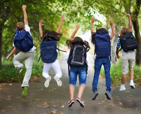 Rear-view of five children jumping in the air wearing backpacks