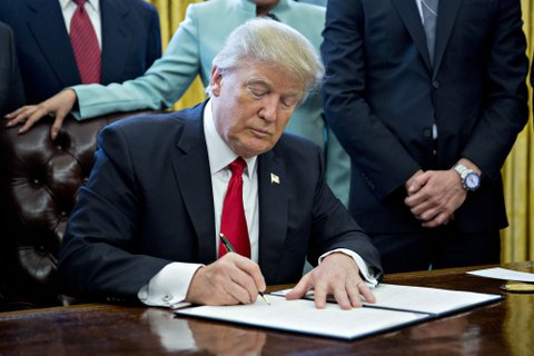 WASHINGTON, DC - JANUARY 30:  (AFP OUT) U.S. President Donald Trump signs an executive order in the Oval Office of the White House surrounded by small business leaders January 30, 2017 in Washington, DC. Trump said he will ÒdramaticallyÓ reduce regulations overall with this executive action as it requires that for every new federal regulation implemented, two must be rescinded. (Photo by Andrew Harrer - Pool/Getty Images)