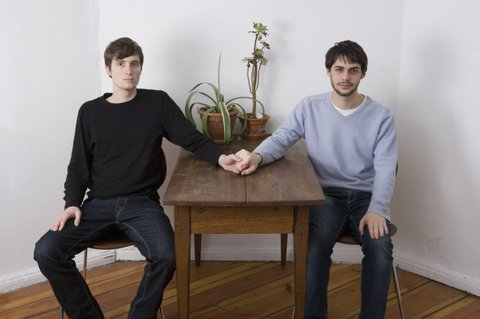 Young gay couple holding hands across table