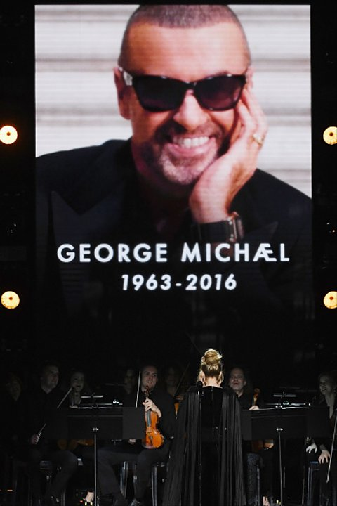 LOS ANGELES, CA - FEBRUARY 12:  An image of the late George Michael is projected on a video screen while recording artist Adele performs onstage during The 59th GRAMMY Awards at STAPLES Center on February 12, 2017 in Los Angeles, California.  (Photo by Kevin Winter/Getty Images for NARAS)
