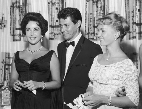 1958: American singer Eddie Fisher, wearing a tuxedo, stands with arm around his wife, American actor Debbie Reynolds (R) and smiles while looking at British-born actor Elizabeth Taylor, smoking a cigarette, Las Vegas, Nevada. The next year Fisher left Reynolds and married Taylor. (Photo by Hulton Archive/Getty Images)