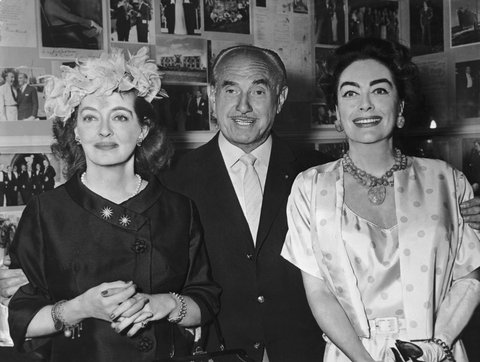 circa 1962:  Left to right: American actor Bette Davis (1908 - 1989), Canadian movie producer Jack L Warner (1892 - 1978), and American actor Joan Crawford (1904 - 1977) pose for a photo. Both actors starred together in the Warner Brothers' film 'Whatever Happened to Baby Jane?' in 1962.  (Photo by Hulton Archive/Getty Images)