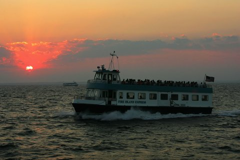 FIRE ISLAND, NY - SEPTEMBER 2:  The Fire Island Express heads to Fire Island Pines from Sayville at sunset on September 2, 2005 on the Fire Island Ferry off the coast of Long Island in New York.  Ferry service to Fire Island began in 1856; passengers could take the Long Island Railroad from Brooklyn to Thompson (now Brentwood), get a stage to Islip, and get on the waiting ferry. Nearly 150 years later, transportation to Fire Island is basically the same. Although there are more ferries from different locations, you do have to take a ferry to get to most parts of Fire Island. Fire Island,  which is the only developed barrier island in the United States without roads, is located 45 minutes outside of New York City, just a 30 minute ferry ride across the Great South Bay. Fire Island is a premier getaway spot for families and friends. Sand dune beaches rollout into the Atlantic Ocean on the south side of the island, while the north side has dining and bars overlooking the bay.  (Photo by Ezra Shaw/Getty Images)
