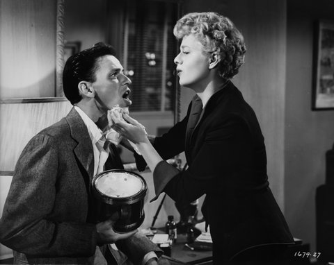 American actress Shelley Winters (1920 - 2006) tends to Frank Sinatra's bruised jaw in a scene from the film 'Meet Danny Wilson', 1951. (Photo by Universal Pictures/Archive Photos/Getty Images)