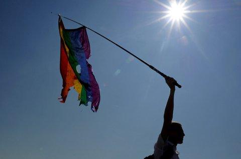 A gay rights activist waves a damaged rainbow flag during a gay pride in St. Petersburg on July 26, 2014. AFP PHOTO / OLGA MALTSEVA        (Photo credit should read OLGA MALTSEVA/AFP/Getty Images)