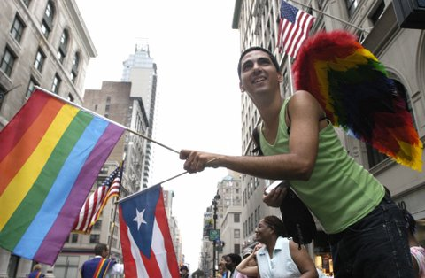 New York, UNITED STATES:  Raynell Valencia waves a gay pride and a Puerto Rican flag as he watches the 36th annual Lesbian, Gay, Bisexual, and Transgender (LGBT) Pride March in New York 25 June 2006. Thousands of marchers from New York's homosexual community took part in the city's annual Gay Pride parade, although high spirit were dampened slightly by recent conservative efforts to reverse political gains by US gays and lesbians. AFP PHOTO/Nicholas ROBERTS  (Photo credit should read NICHOLAS ROBERTS/AFP/Getty Images)