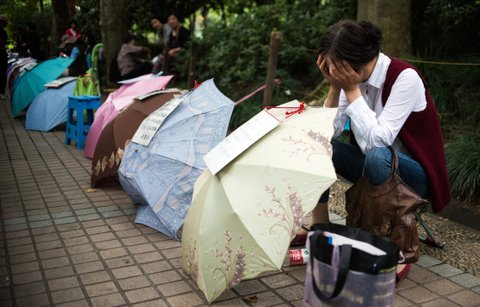 A Chinese woman rests behind her advertising notice set up on an umbrella to attract other parents while looking for a partner for her child at a marriage market in Shanghai on May 30, 2015. China's one child policy has also created a severe gender imbalance due to a traditional preference for sons. Nearly 116 boys were born for every 100 girls in China in 2014, while the sex ratio in the total population was 105 men to 100 women. AFP PHOTO / JOHANNES EISELE        (Photo credit should read JOHANNES EISELE/AFP/Getty Images)