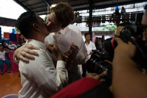 MANILA, PHILIPPINES - JUNE 28:  Filipino Jesus Bacsal (L) and U.S. national Michael Ellis (R) kiss before a crowd of photographers during a mass 'wedding rites' on June 28, 2015 in Manila, Philippines. A small Christian ecumenical group officiated the wedding of one gay and 14 lesbian couples in simple ceremony rites held in a basketball court in the middle class district of Quezon City. Same sex marriage unions are not officially recognized under Philippine laws and is staunchly rejected by the dominant Catholic church in the Philippines. Organizers said todays rites had a special relevance following the landmark U.S. Supreme Court ruling on gay marriage and emboldens other countries to adopt a more tolerant stance on same sex unions.  (Photo by Dondi Tawatao/Getty Images)