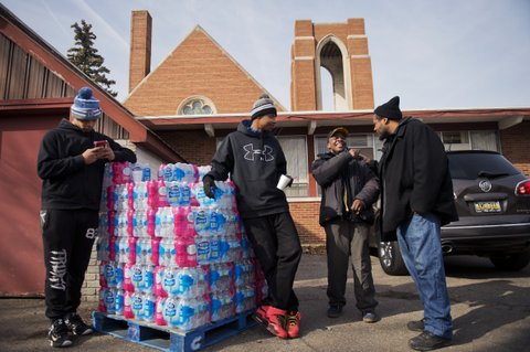 UNITED STATES - FEBRUARY 23: From left, Immanuel Stinson, Tirrell Mills, Walter Simmons, and Charles Reid, man a water distribution area at the St. Mark Baptist Church in Flint, Mich., February 23, 2016. The water supply was not properly treated after being switched from Lake Huron to the Flint River and now contains lead and iron. (Photo By Tom Williams/CQ Roll Call)